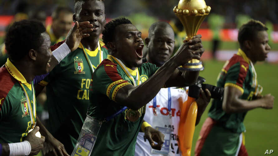 Cameroon players run celebrating with the trophy after winning the African Cup of Nations final soccer match between Egypt and Cameroon at the Stade de l'Amitie, in Libreville, Gabon, Sunday, Feb. 5, 2017.