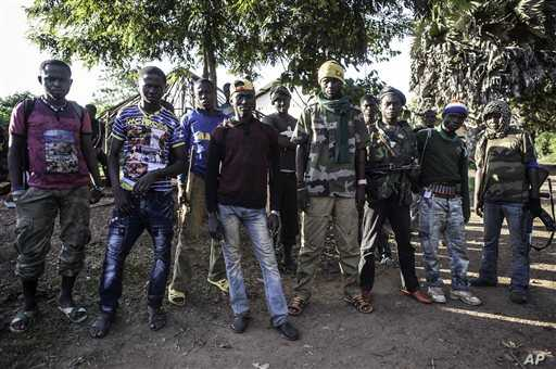 In this Aug. 28, 2014, photo an Anti-Balaka group that defends the Christian neighborhood near the Church of the city stands for a photo in Boda, Central African Republic. More than 5,000 people have died in sectarian violence in the Central African