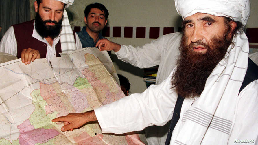 FILE - Jalaluddin Haqqani, right, the Taliban's Minister for Tribal Affairs, points to a map of Afghanistan during a visit to Islamabad, Pakistan, Oct. 19, 2001, as his son Naziruddin, left, looks on.