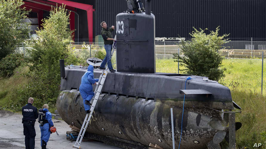 FILE - Police technicians board Peter Madsen's submarine UC3 Nautilus, Aug. 13, 2017, on a pier in Copenhagen harbor, Denmark. A Danish prosecutor said Tuesday Jan. 16, 2018  that inventor Peter Madsen has been charged with murdering Swedish journali
