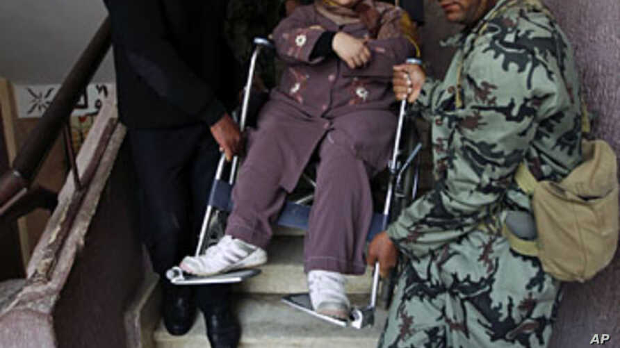 A woman on a wheelchair is helped down the stairs by army soldiers and policemen after casting her vote on the second day of  parliamentary elections in Cairo November 29, 2011