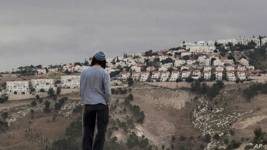 FILE - A Jewish settler looks at the West bank settlement of Maaleh Adumim, from the E-1 area on the eastern outskirts of Jerusalem. West Bank settlement construction surged during the first year of the Trump presidency, an Israeli monitoring group s