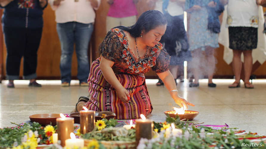 FILE - A woman performs a ritual celebration before a meeting in Lima, Peru, of delegations of indigenous women from over 20 countries of North, Central and South America, March 3, 2015, ahead of the yearly session of the U.N. Commission on the Statu