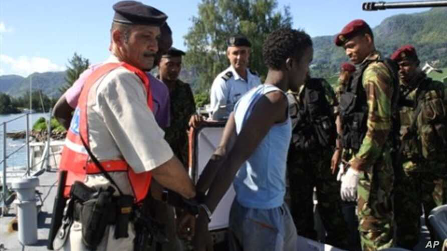 An arrested Somali pirate is handcuffed by police upon his arrival in Port Victoria, 31 Mar 2010, with the six Seychellois fishermen, who were taken hostage by Somali pirates
