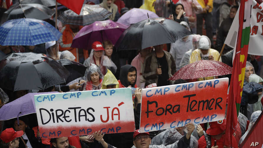 """Demonstrators march against Brazil's President Michel Temer, holding banners that reads in Portuguese """"Temer Out"""", and """"Elections Now"""", in Sao Paulo, Brazil, May 21, 2017."""
