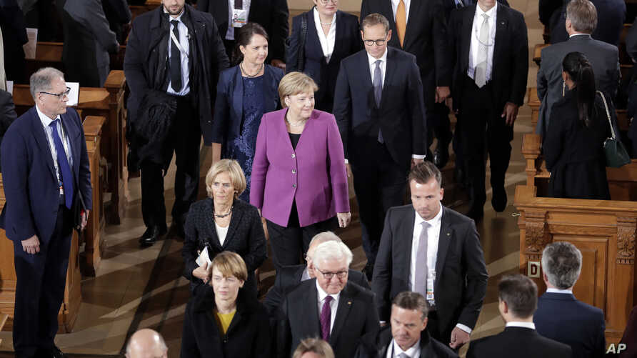 German Chancellor Angela Merkel, center, leaves the Berlin cathedral after an ecumenical mass as part of the German Unification Day public festival in Berlin, Germany, Oct. 3, 2018.