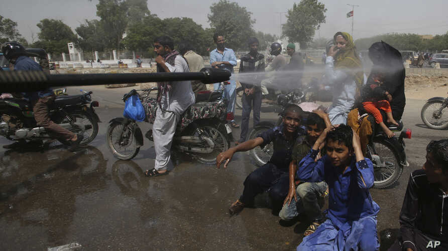 A Pakistani volunteer sprays water on people to keep them cool as temperatures reached 43 Celsius (109.4 Fahrenheit) in Karachi, Pakistan, May 21, 2018.