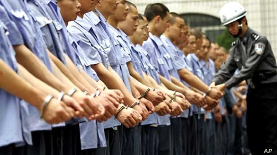 Guard checks handcuffs on group of prisoners in Chongqing (file photo)