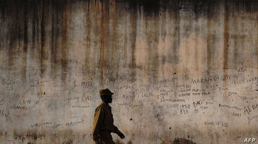 FILE - A prison guard walks along a perimeter wall at a prison in Rumbek, Lakes state, South Sudan, Feb. 19, 2014.