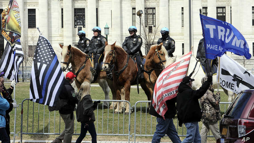 Members of the Albany police department mounted unit offer a police presence as gun rights activists with the National Constitutional Coalition of Patriotic Americans take part in a national rally aimed at pushing back against calls for stronger gun