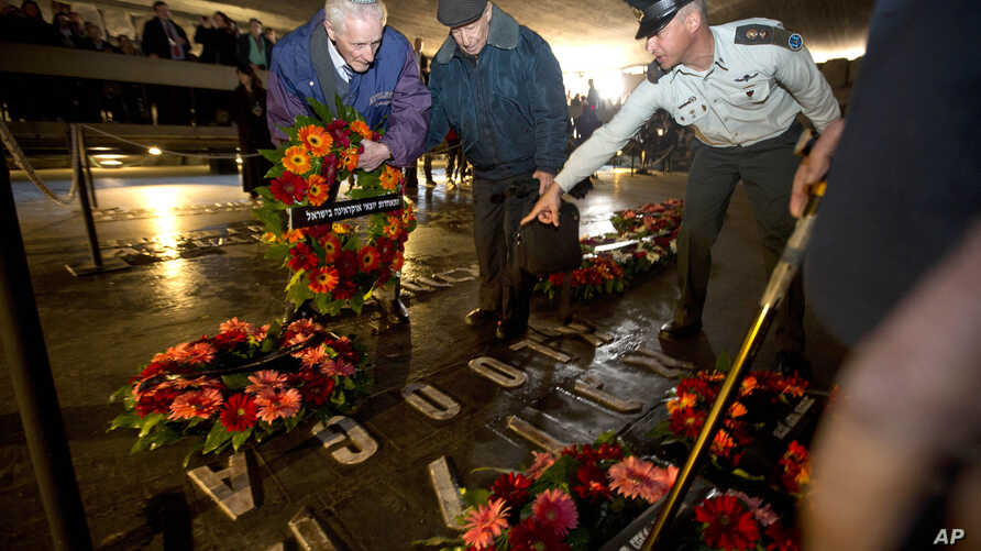 Holocaust survivors and their relatives lay a wreath next to the names of concentration camps during a ceremony marking the annual Holocaust Remembrance Day in Jerusalem, April 16, 2015.