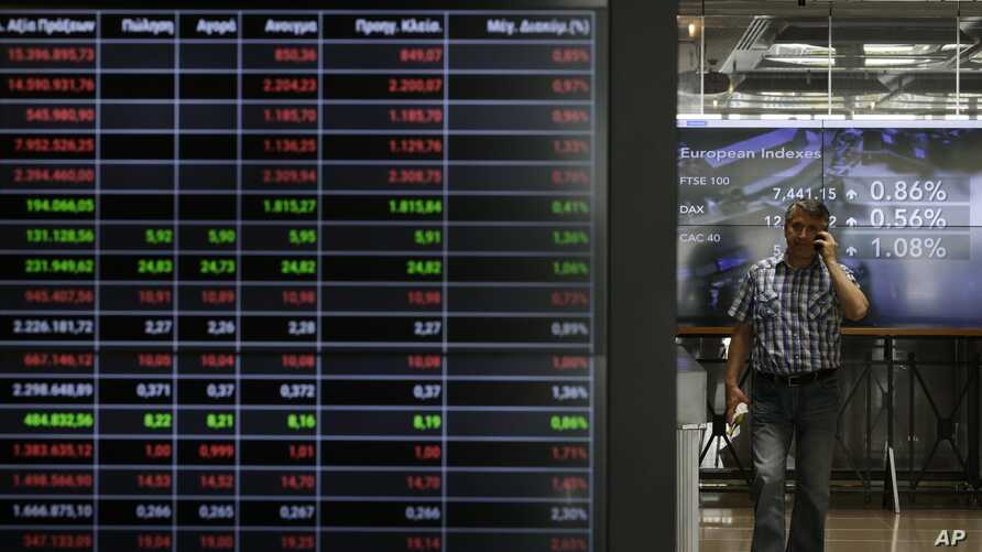 A man speaks his on his cellphone next to an index board at the reception hall of the Stock Exchange in Athens, July 25, 2017. Greece tapped international bond markets for the first time in three years on July 25, 2017.