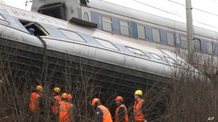 Workers inspect a damaged railway carriage not far from the village of Uglovka in Russia's Novgorod region on November 28, 2009, as it traveled between Moscow and Saint Petersburg