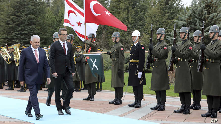 Turkish Prime Minister Binali Yildirim, left, and Tufan Erhurman, the prime minister of the self-declared Turkish Cypriot state in the north of the divided island, review a military honour guard during a ceremony at the Cankaya Palace in Ankara, Turk