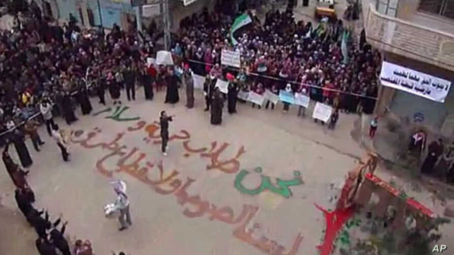 """In this image from amateur video made available by the Shaam News Network and shot on Friday, December 30, 2011, protesters gather in Homs, Syria. The writing on the ground, in Arabic, reads: """"We are those who seek freedom and peace. We are not thiev"""