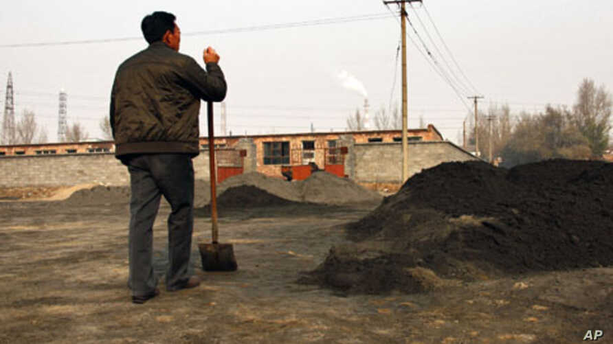 A villager looks towards a rare earth smelting plant as he takes a break from shoveling cast-off tailings of crushed mineral ore that contain rare earth metals in Xinguang Village, (File)