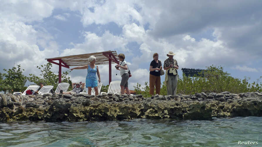 """U.S. """"people-to-people"""" tourists stand beside a natural sea pool in the Zapata Swamp in southern Cuba, April 7, 2012."""