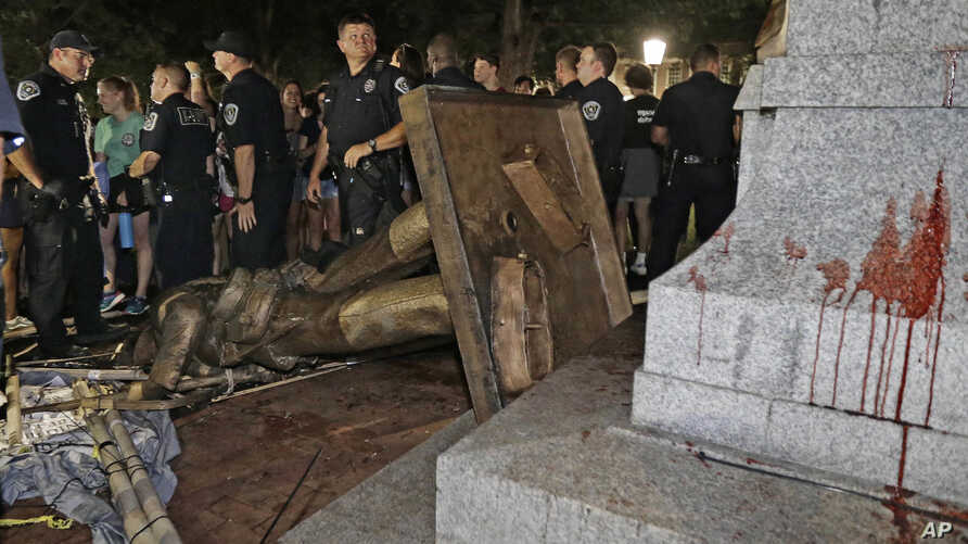 FILE - police stand guard after the confederate statue known as Silent Sam was toppled by protesters on campus at the University of North Carolina in Chapel Hill, N.C.
