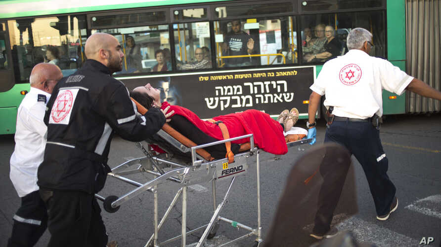 Israeli rescue personal evacuate a woman from a stabbing attack site in Rishon Lezion, Israel, Monday, Nov. 2, 2015.