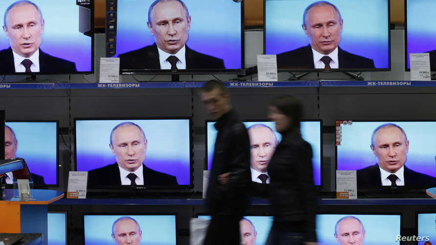 FILE - Visitors walk past TV sets during Russian President Vladimir Putin's live broadcast nationwide phone-in at the DNS electronic shop in Russia's Siberian city of Krasnoyarsk, April 17, 2014. Putin will take to live TV Thursday to try to fix some