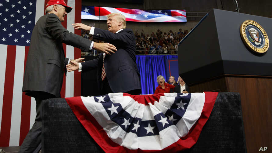 President Donald Trump gets ready to embrace U.S. Senate candidate Luther Strange during a campaign rally, in Huntsville, Alabama, Sept. 22, 2017.