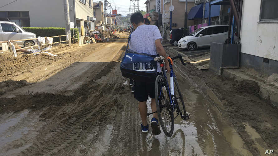 A man carries his bicycle on a mud-covered street in Hiroshima, southwestern Japan, Wednesday, July 11, 2018.