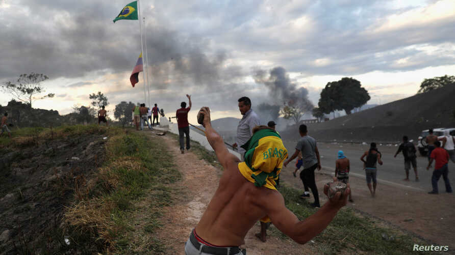 People hurl stones at the border between Venezuela and Brazil in Pacaraima, Brazil, Feb. 23, 2019.