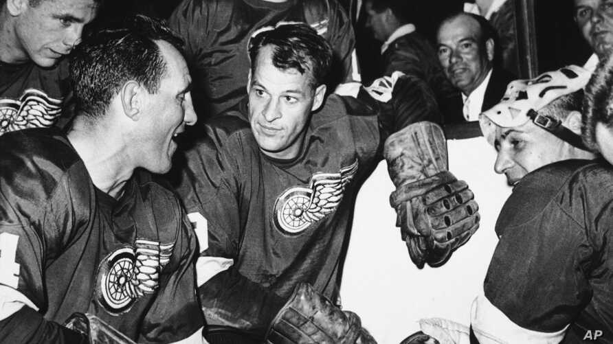 FILE - Detroit Red Wings star forward Gordie Howe is surrounded by teammates as he kneels after scoring his 544th goal to tie the National Hockey League all-time record, in Detroit, Oct. 27, 1963.