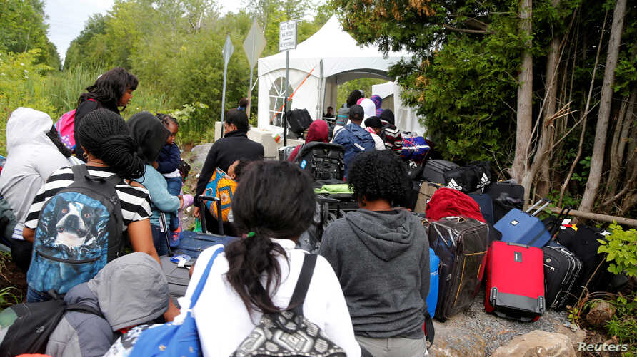 FILE - A line of asylum seekers who identified themselves as from Haiti wait to enter into Canada from Roxham Road in Champlain, New York, Aug. 7, 2017.