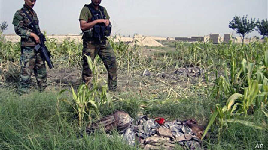 Afghan National Army soldiers stand near bodies of two suicide attackers near a NATO base in Khost province of Afghanistan, 28 Aug 2010
