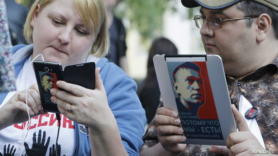 Opposition activists use electronic devices pictured with portraits of prominent anti-corruption blogger Alexei Navalny during a four day-long protest in a boulevard in central Moscow May 10, 2012.