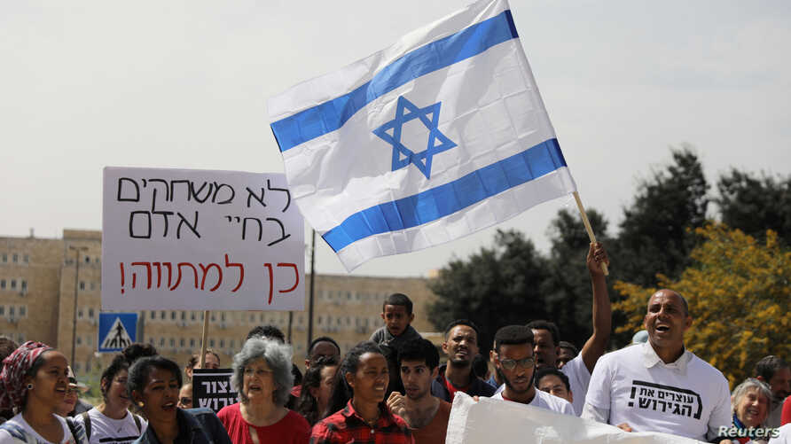 African migrants and Israeli activists demonstrate in support of the new agreement with the U.N. refugee agency to relocate thousands of African migrants, outside Israeli Prime Minister office in Jerusalem, April 3, 2018.
