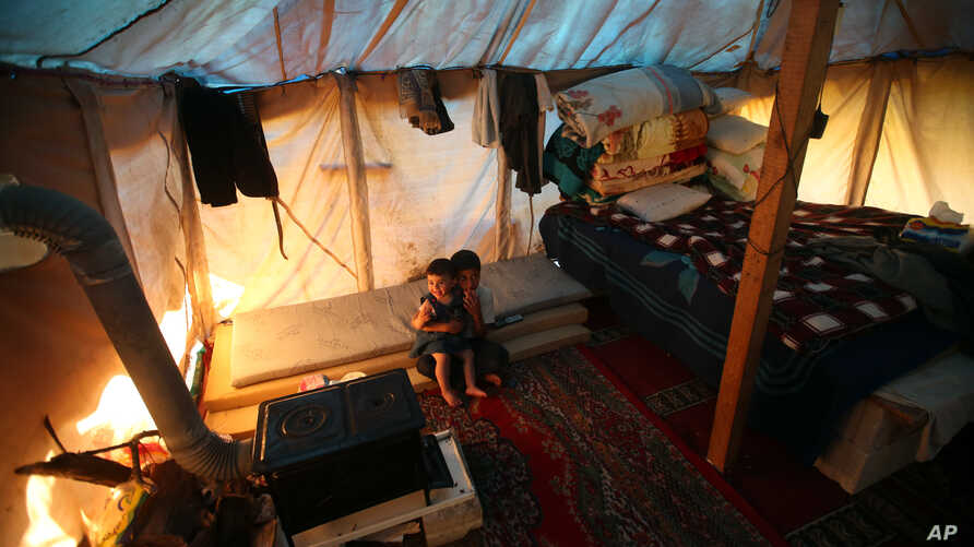 Syrian refugee children sit inside their tent at a small refugee camp, in Ketermaya village southeast of Beirut, Lebanon, March 14, 2013.