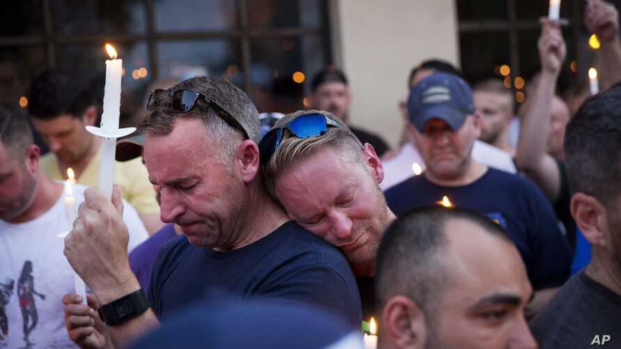 Paul Cox, right, leans on the shoulder of Brian Sullivan, as they observe a moment of silence during a vigil for a fatal shooting at an Orlando nightclub, June 12, 2016, in Atlanta.