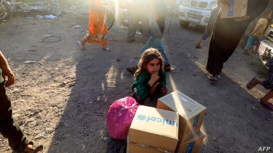 A displaced Syrian child who fled from Raqa, sits behind humanitarian aid boxes delivered by UNICEF at a temporary camp in the town of Tabqa, about 55 kilometres (35 miles) west of Raqa.