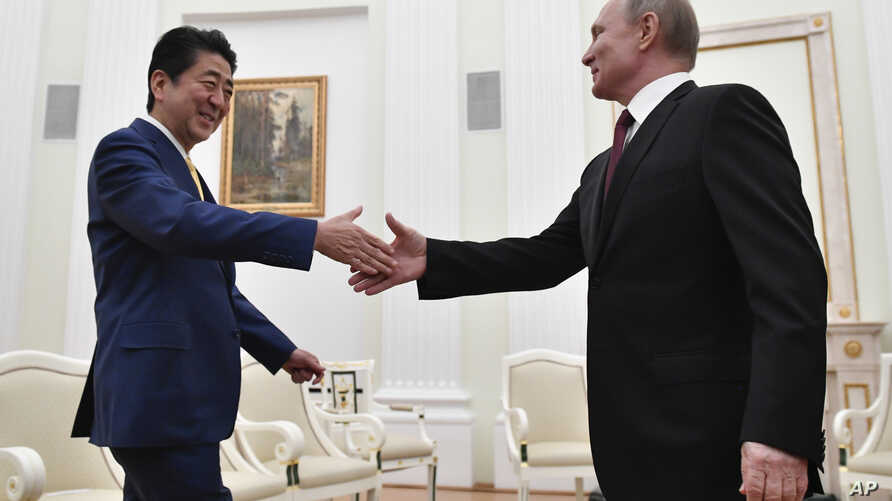 Russian President Vladimir Putin, right, greets Japanese Prime Minister Shinzo Abe prior their talks in the Kremlin in Moscow, Russia, Tuesday, Jan. 22, 2019.