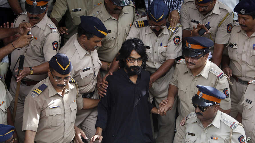 Indian policemen escort political cartoonist Aseem Trivedi, center in black as they leave a court in Mumbai, India, Monday, Sept. 10, 2012.