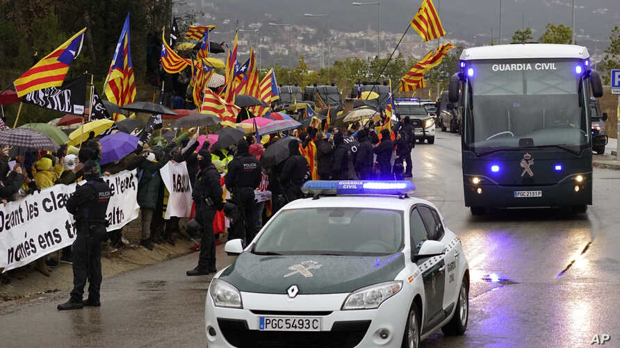 Demonstrators wave esteladas or independence flags as a bus of the Spain's Civil Guard carrying the nine Catalonian politicians and activists, leaves the Brians II prison, in Barcelona, Spain, Feb.1, 2019.