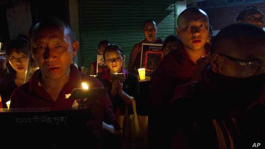 Tibetan exiles participate in a candlelit vigil in Dharmsala, India, Sunday, Sept. 30, 2012.