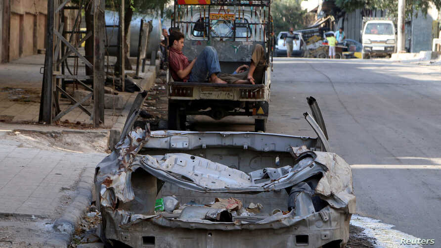 Men rest at the back of a pickup truck near a damaged car in the rebel held al-Katerji district in Aleppo, Syria, Aug. 13, 2016.
