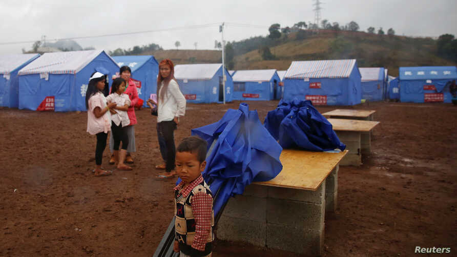 Refugees who fled fighting in neighboring Myanmar stand in a Chinese disaster relief tent camp in the town of Nansan, Yunnan province, China, March 12, 2017.