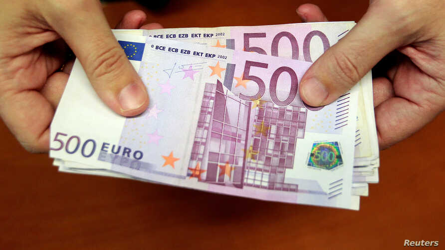 FILE - A bank employee holds a pile of 500 euro notes at a bank branch in Madrid, Jan. 13, 2011.