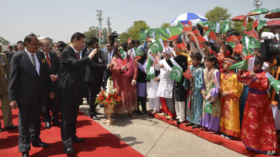 Chinese President Xi Jinping waves to children with Pakistan's Present Mamnoon Hussain, left, upon his arrival at Nur Khan airbase in Islamabad, Pakistan, April 20, 2015.