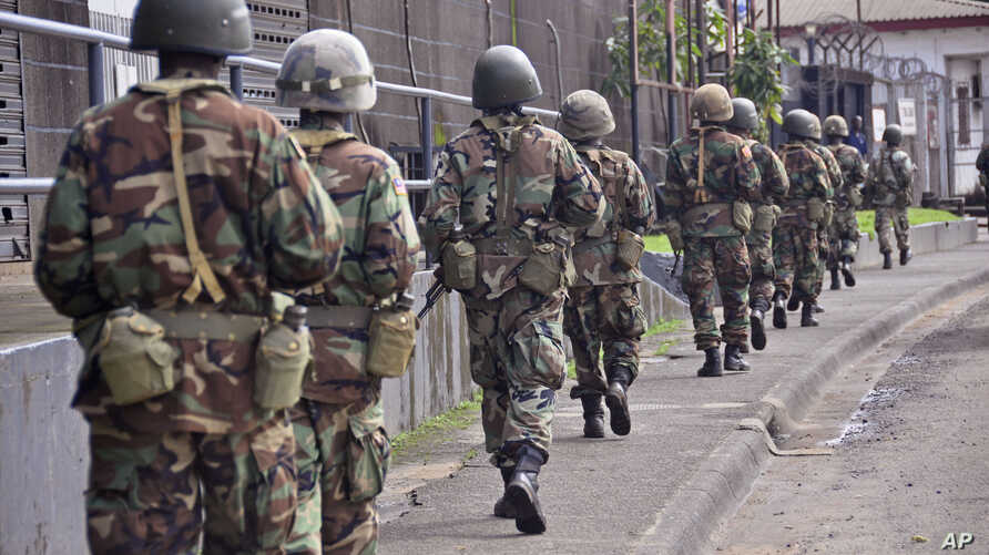 Liberian soldiers walk through streets to prevent panic as fears of the deadly Ebola virus spread in the city of Monrovia, Liberia, Friday, Aug 1, 2014. U.S. health officials warned Americans not to travel to the three West African countries hit by t
