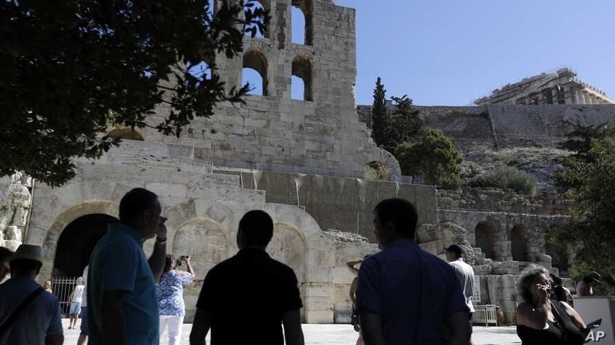 FILE - In this July 6, 2017 photo, tourists take photographs of the Herod Atticus theater and Parthenon temple atop of Acropolis hill during a three-hour work stoppage in Athens.