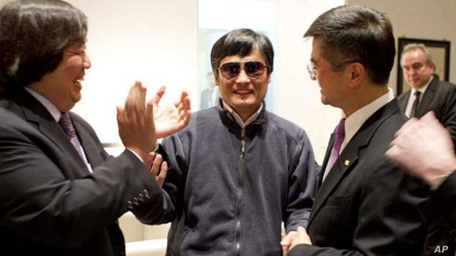 In this photo released by the US Embassy Beijing Press Office, blind lawyer Chen Guangcheng, center, holds hands with U.S. Ambassador to China Gary Locke, right, as U.S. State Department Legal Advisor Harold Koh, left, applauds, before leaving the U.