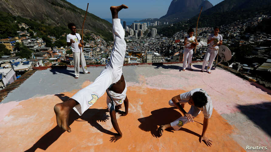Members of the Acorda Capoeira (Awaken Capoeira) group perform on a rooftop in the Rocinha favela in Rio de Janeiro, Brazil, July 24, 2016.