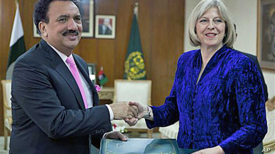Visiting British Home Secretary Theresa May exchanges copies of agreements regarding bilateral issues - including cooperation in the war against terrorism - with Pakistan's Interior Minister Rehman Malik in Islamabad, Pakistan, Oct 26, 2010 (File Pho