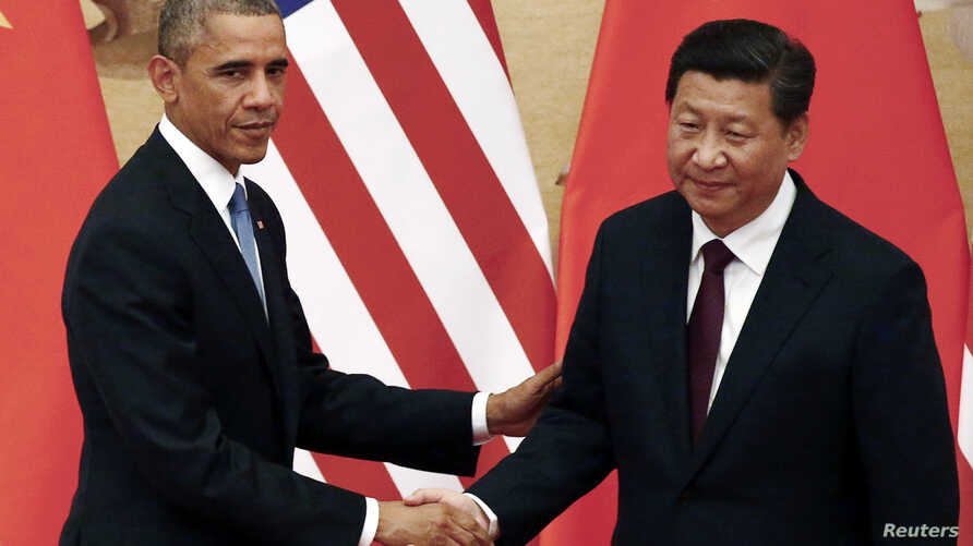 U.S. President Barack Obama (L) shakes hands with China's President Xi Jinping in front of U.S. and Chinese national flags during a joint news conference at the Great Hall of the People in Beijing Nov. 12, 2014.