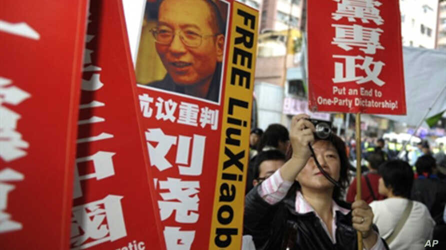 A pro-democracy demonstator takes a photograph next to a portrait of mainland dissident Liu Xiaobo during a demonstration in Hong Kong, 1 Jan. 2010.